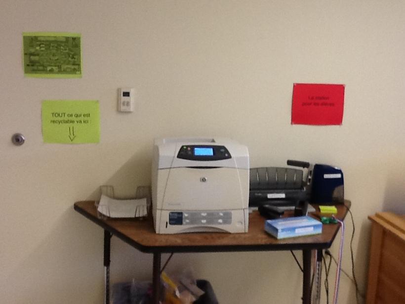 près de la porte, l'imprimante que je partage avec le département de langues (elle est wifi), et une petite station pour les élèves avec des ciseaux, une agrafeuse, du scotch, etc. En dessous, une poubelle de recyclage.