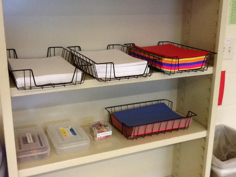 de l'autre côté de la porte, une étagère avec des feuilles blanches et de couleurs pour la photocopieuse et pour des projets artistiques éventuels, une boite avec des crayons de couleurs -- dans la boite vide il y aura des ciseaux mais ils ne sont pas encore arrivés.